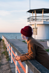 Girl in hat on pier at sunrise