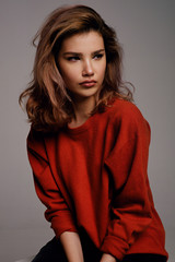 Serious brunette woman in red sweater looking away