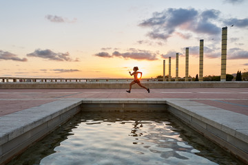 Sportswoman running at sunset