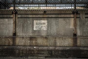 Grungy wall protecting urban subway tracks
