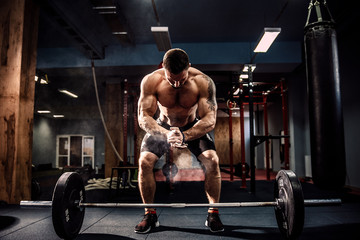 Muscular fitness man preparing to deadlift a barbell over his head in modern fitness center.Functional training.Snatch exercise Wall mural