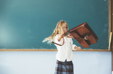 Girl throwing backpack in classroom