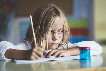 Thoughtful girl writing in class
