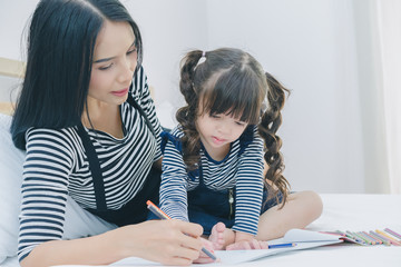 A little cute girl enjoy drawing into the book by colorful pastel with mother on the white bed in the bedroom, education time at home