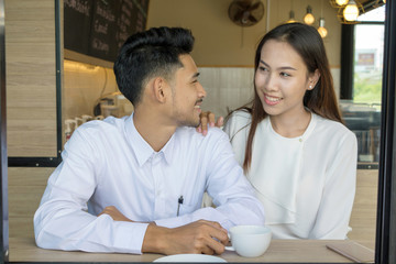 Asian young couple in love at a coffee shop