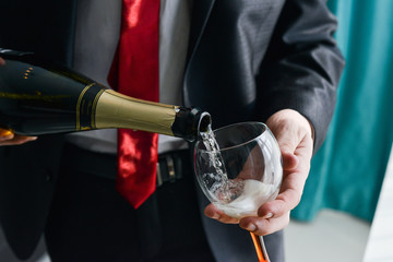 man filling decorated glass with champagne
