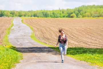 Young woman running, jumping in air and smiling on countryside dirt road by brown plowed fields with furrows in summer in Ile D'Orleans, Quebec, Canada
