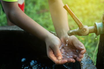 Child use hand the water frame to drink ,Water shortage concept.