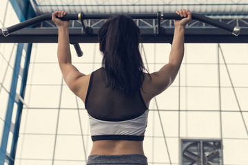 Fitness woman exercising on chin-up bar. Athlete girl doing chin-ups training