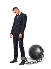 A sad businessman looks down while shackled to a large iron ball with a chain to his ankle.