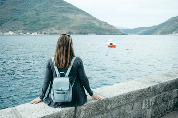 Back view of Young woman in gray cardigan and blue backpack sits near the sea and mountains, Montenegro