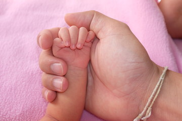 concept of love and family. Adult and baby hands.