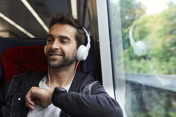 Dude with phones on train, looking away and smiling