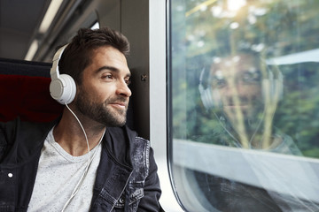 Guy enjoying travel by train, smiling