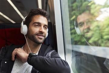 Guy listening to headphones on train, smiling