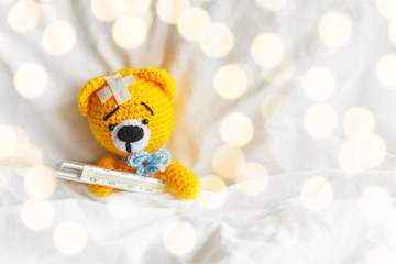 Yellow teddy bear with thermometer and plaster on head in white bedroom.