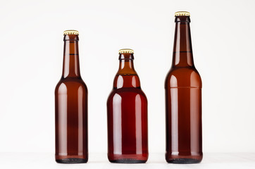 Garden Poster Beer / Cider Set of different brown beer bottles 500ml and 330ml mock up. Template for advertising, design, branding identity on white wood table.