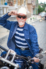 A man on a motorcycle, wearing a cowboy hat.