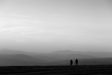 A couple on top of a mountain at near sunset, with soft tones and distant hills and mountains