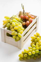 Closeup of green grapes in a wooden box on white background