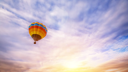 Colorful hot air balloon flying over the sky as background at sunrise