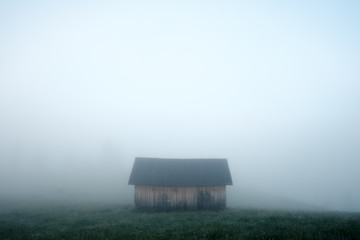 Remote house on foggy meadow