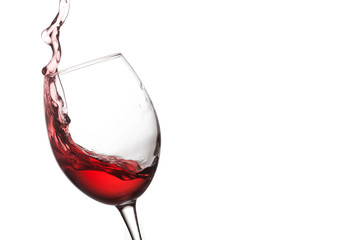 Red wine splashing. Pouring wine into crystal glass, close-up, white background. copy space.