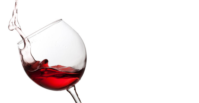 Splashing red wine in crystal wineglass. white background. copy space photo