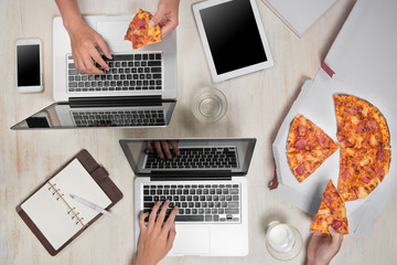 Top view of business people working at office desk and having a lunch break with a tasty pizza