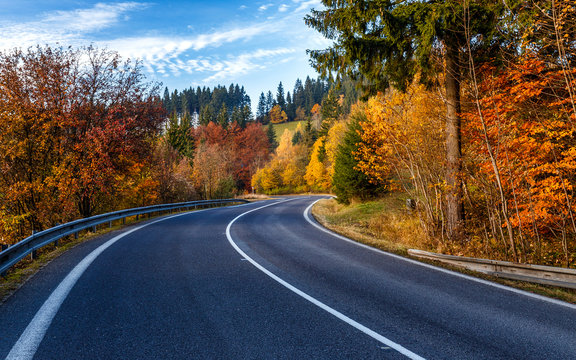 Turn on the road through the forest in autumn country
