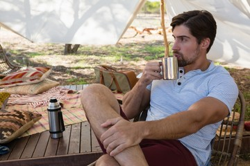 Thoughtful man drinking coffee in tent