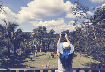 Beautiful Woman In Hat Making Photo Picture Of Tropical Forest On Cell Smart Phone From Hotel Balcony Or Terrace Back Rear View
