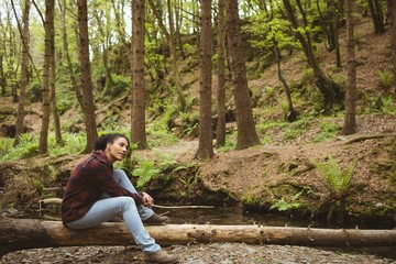 Young woman sitting on fallen tree at forest