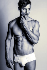 Underwear concept. Handsome muscular male model in trendy white underwear posing over grey background. Studio shot