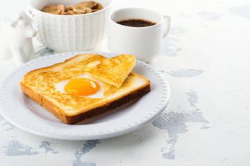Breakfast for Valentines day: toast with heart shaped egg, muesli and coffee on white concrete table. Space for text