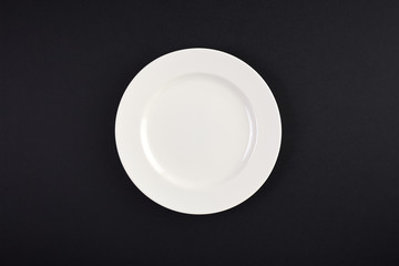 Top view of clean white dish on background of black table