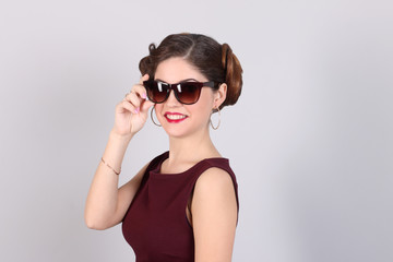 Beautiful smiling woman with hairdo and in sunglasses poses in white studio
