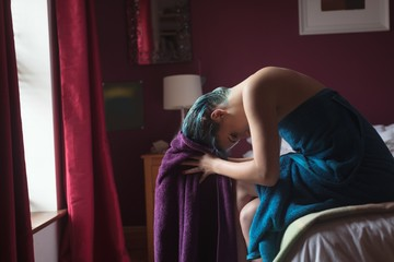 Woman drying hair with towel on bed