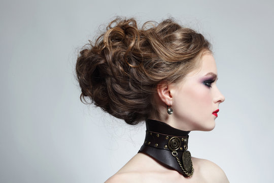 Profile portrait of young beautiful girl with stylish hairdo and fancy steampunk collar