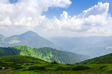 Travel, trekking. Summer landscape - mountains, green grass, trees and blue sky. Horizontal frame