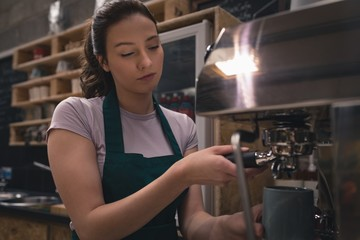 Waitress taking coffee from espresso machine