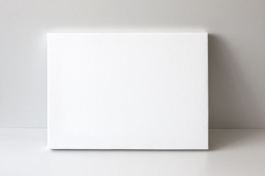 White empty canvas. Gray wall on background. Mock up poster frame, canvas template.