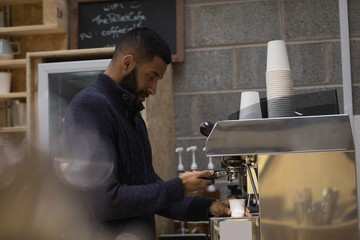 Male owner making coffee in cafe