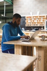 Man using laptop while sitting at table in coffee shop