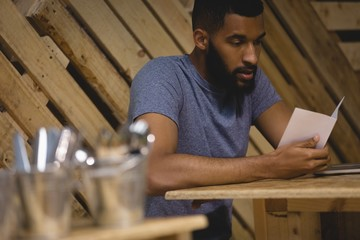 Young man reading paper in cafe