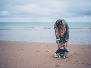 Mother helping baby walk on beach