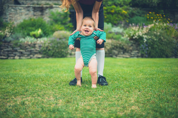 Mother helping baby walk on lawn
