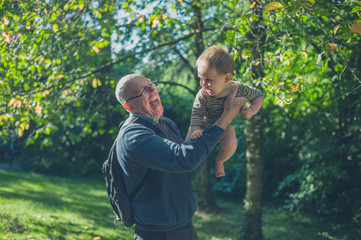 Senior man lifting baby grandson in nature