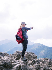 A woman at the top of the mountain takes pictures on a smartphone