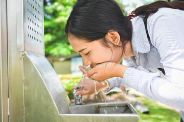 Women drinking water tap in park